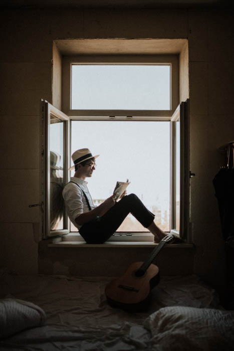 A male model posing indoors on a window sill - fashion photography composition