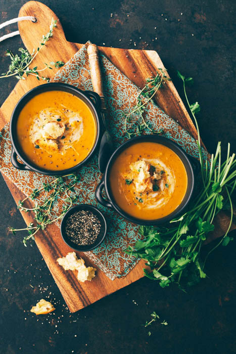 two bowls of carrot ginger soup served on a wooden cutting board