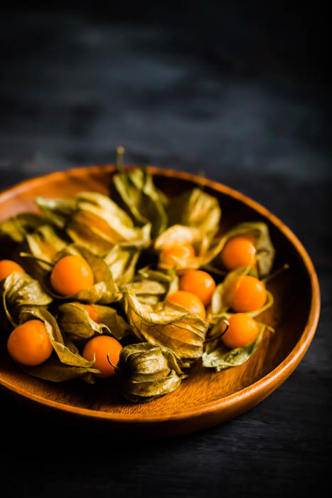 close up of a plate of gooseberries on dark background