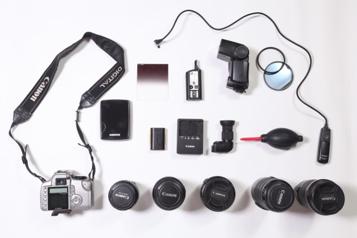 A flat lay of various travel photography accessories