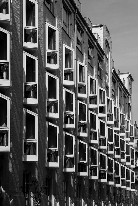 black and white urban photograph of a tall multi windowed building