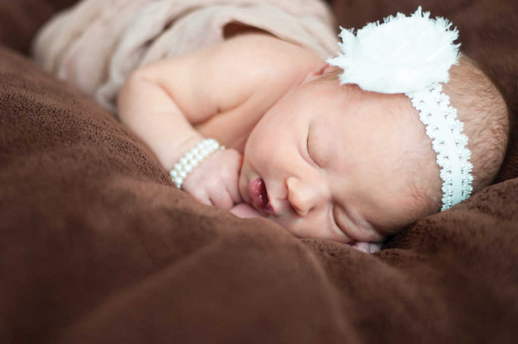 close up portrait of a newborn baby on brown material, wearing a pearl headband and bracelet. newborn photography