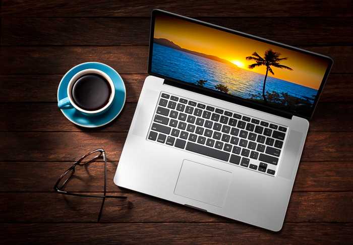 a laptop with sunset screensaver, glasses and coffee cup on a wooden table.