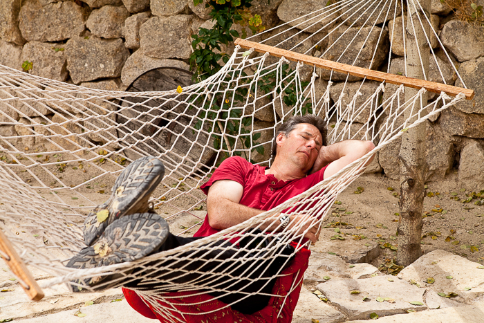 a man in a red t-shirt asleep in a netted hammock - avoid the travel photography mistakes of treating a trip as just a holiday