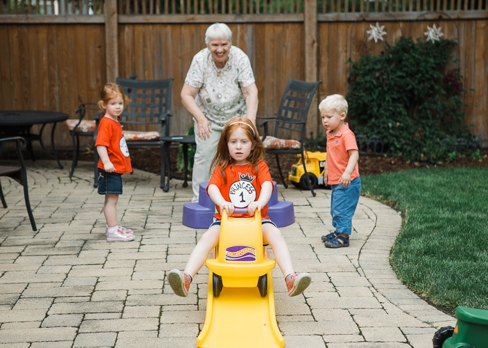 Candid lifestyle photography of a grandmother playing outdoors with three young grandchildren