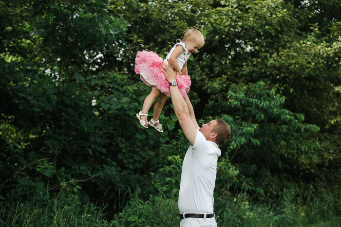 playful lifestyle photography family portrait of a father holding a little girl in pink tutu above his head in a leafy outdoor setting
