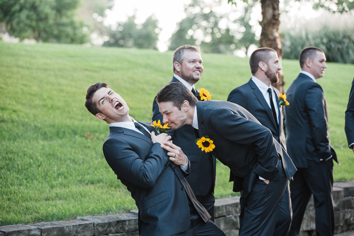 A humourous wedding photo depicting a group of groomsmen, one smelling the sunflower in another mans lapel