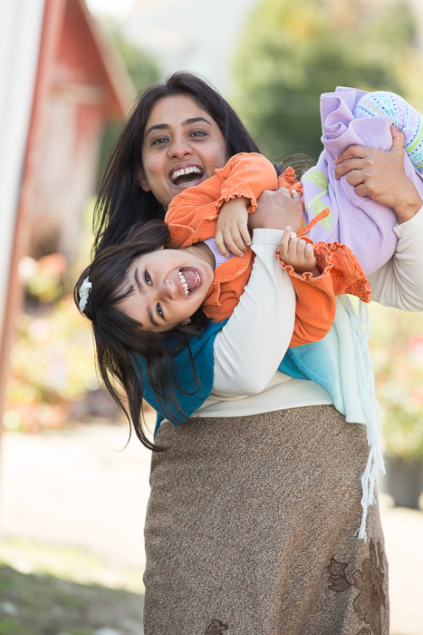 Lifestyle photography portrait of a mother holding her daughter playfully upside down, both smiling towards the camera