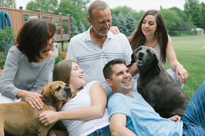 Natural lifestyle photography shot of a family lying on the grass with their two dogs