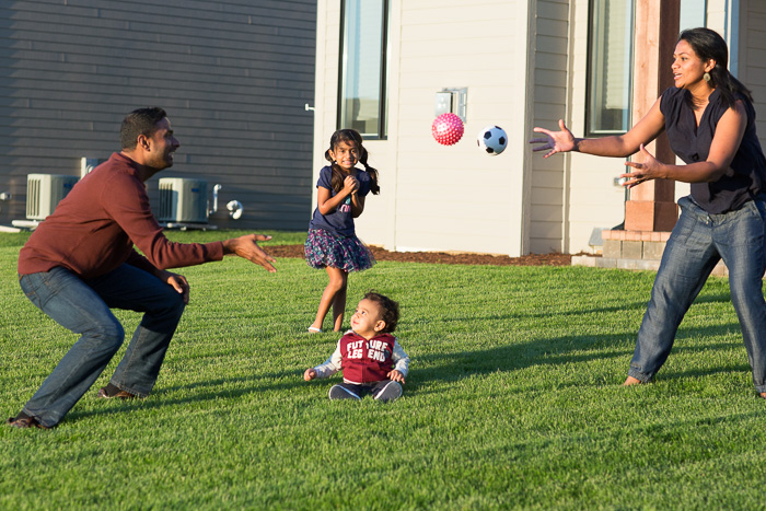 candid lifestyle photograph of a father and mother playing catch with two young children in the garden