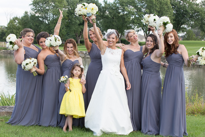 Playful wedding lifestyle shot showing the bride with 7 bridesmaids and 1 flower girl holding bouquets of white flowers in the air
