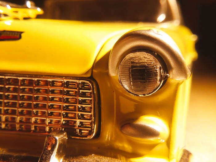 close up iphone photo of yellow car headlight