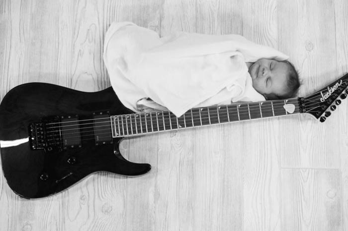 Black and white photo of newborn photographed near a guitar. newborn photography poses