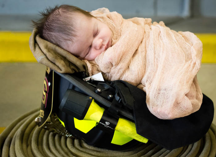 newborn baby photographed in a firefighter helmet. newborn photography poses