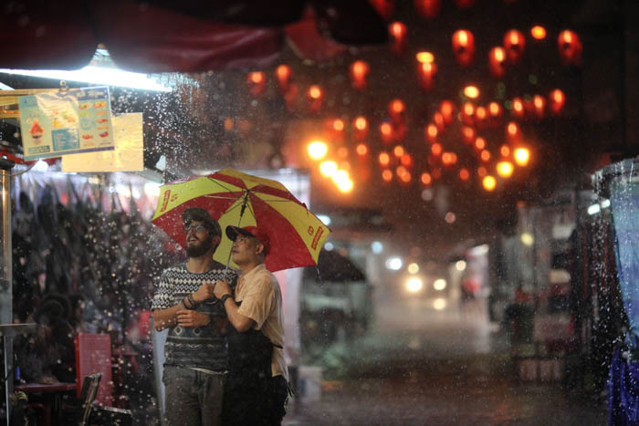 Two men in a rainy outdoor market at night, lit by colorful lanterns