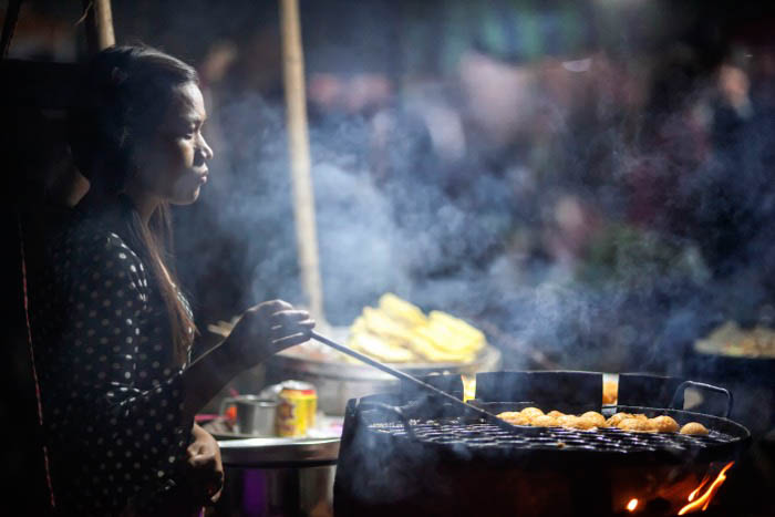 A night street photography shpt of a street food vendor at work