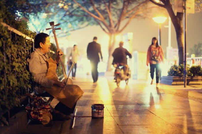 A street musician playing a stringed instrument on the city street at night