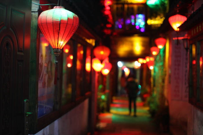 A night street photo of an alley lit by colorful lanterns