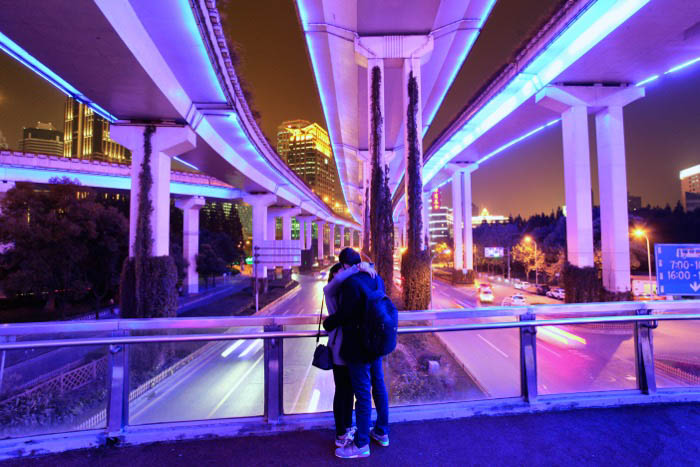 city street night photography of a couple embracing under a modern bridge