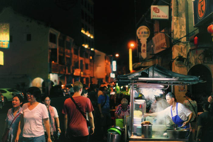 A night street photo of food stalls and passers by