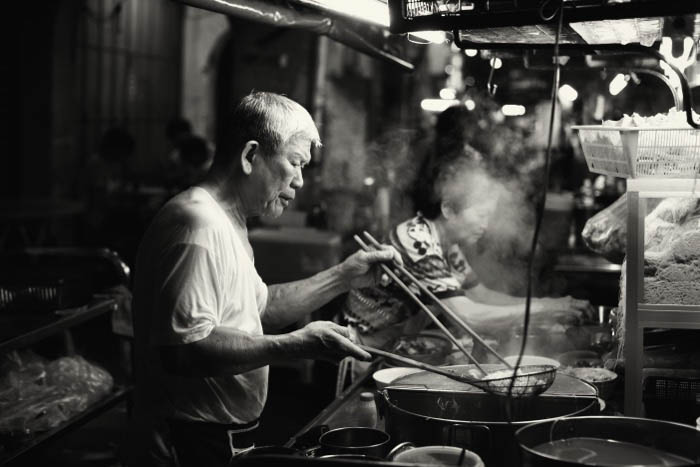 City street night photography shot of a man cooking in a food stall