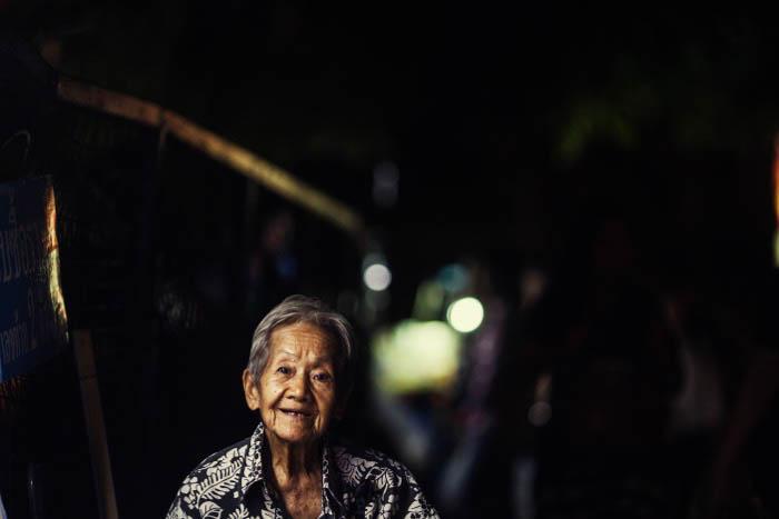 A city street night portrait of an elderly woman