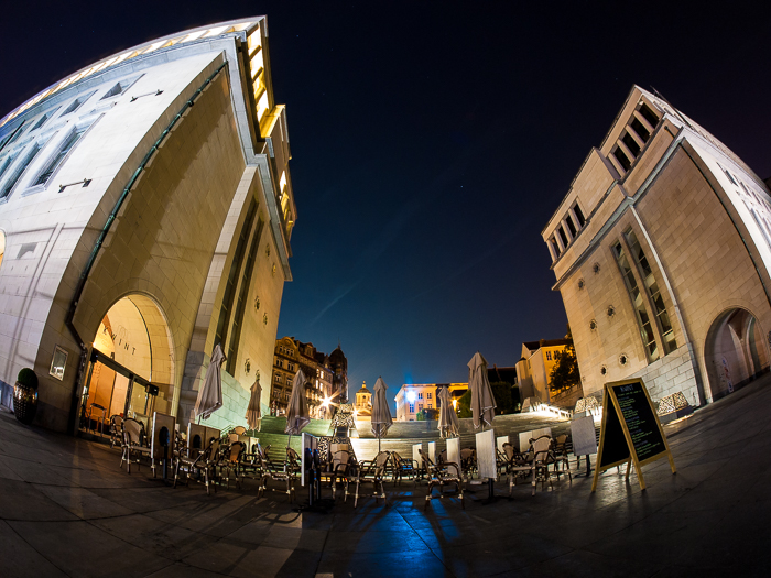 powerful distorted image of two tall buildings framing a plaza area of tables and chairs at night, urban photography taken with fisheye lens