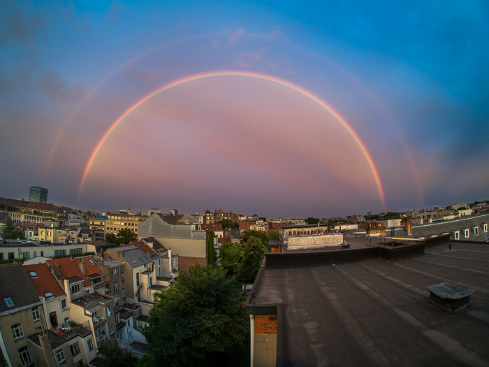 beautiful pink double rainbow against a bright blue sky over an urban rooftop cityscape