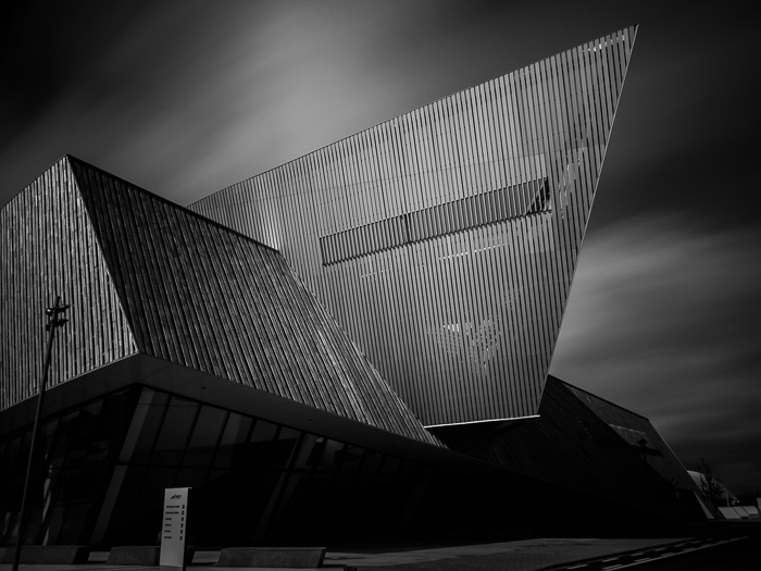 long exposure black and white photo of The Congress Centre in Mons (Belgium), standing against a dynamic sky with fast moving clouds
