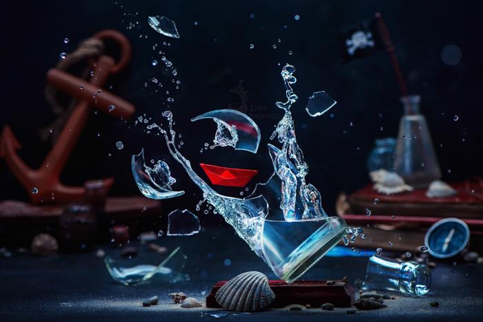 Natureza morta de um copo de água quebrando cercado por objetos com tema marinho