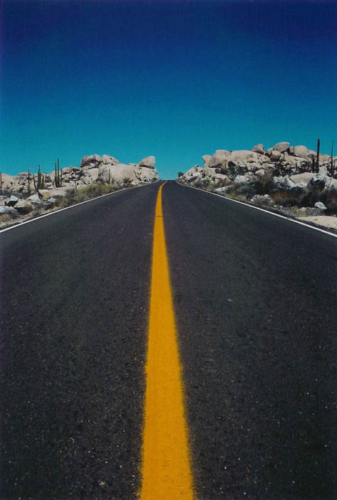 road photo of a highway leading into the horizon, blue sky and yellow striped road