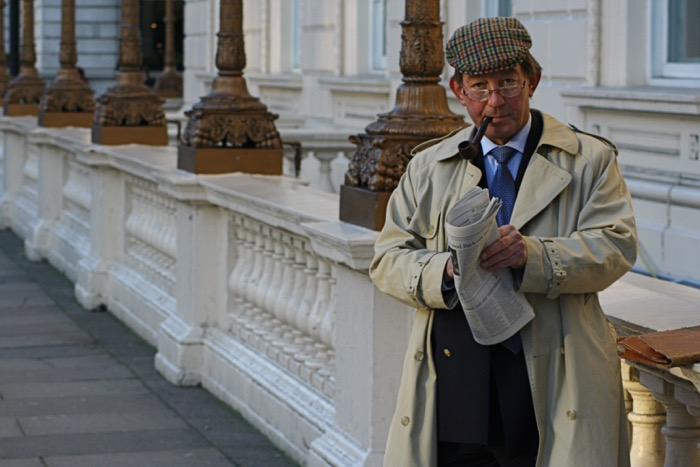 London gentleman in peaked cap and glasses, smoking a pipe and reading the newspaper in an outdoor urban setting