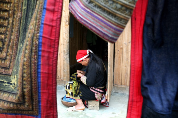 Travel photography showing a Vietnamese lady sitting down while working with textiles, framed by coloured materials hanging in the foreground