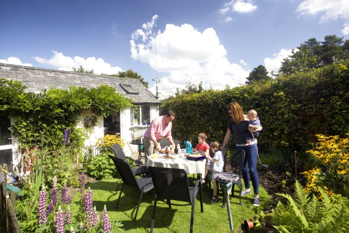 Family eating dinner outdoors in a small sunny garden with flowers