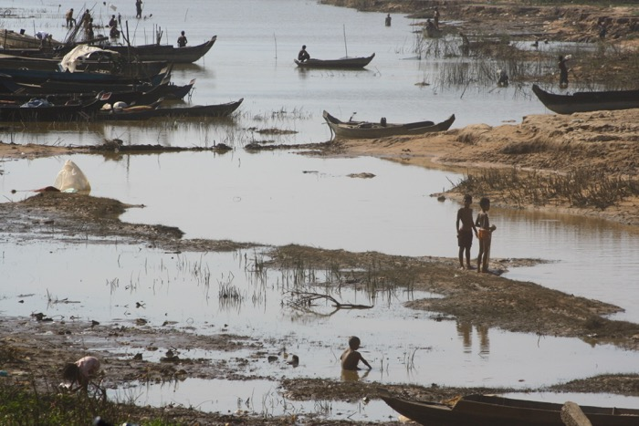 Travel photography showing people living in extreme poverty. River scene with wooden fishing boats and people