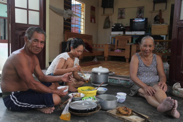Vietnamese family eating dinner on the floor in the interior of their house.