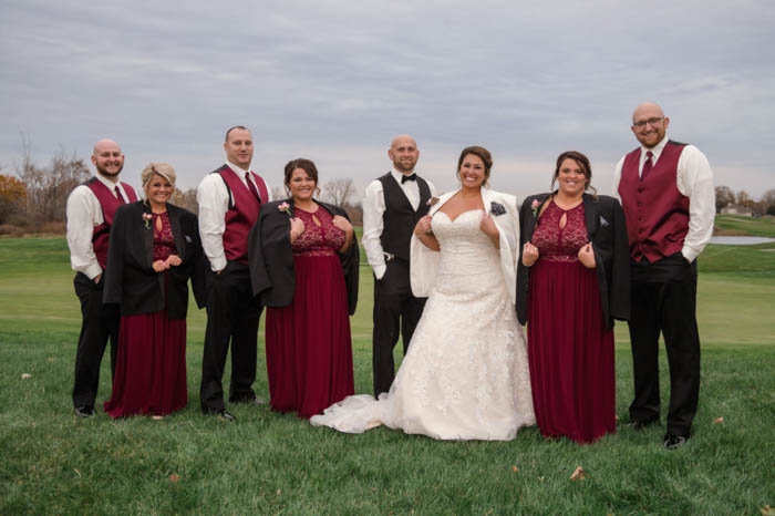 bridesmaids and bride wearing the groomsmen and groom's suit jackets in a twist on the classical bridal party pose