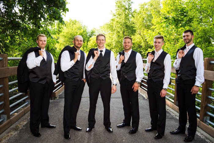 groomsmen and groom group photo, holding suit jackets over shoulder