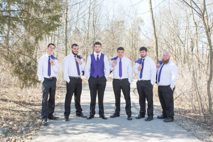 classic groom and groomsmen pose with the groomsmen holding their suit jackets over one shoulder