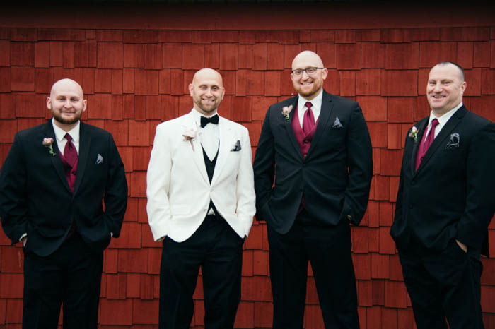 groom and groomsmen posing together with hands in their pockets against a red brick wall