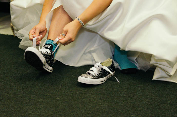 details photo of a bride tying up the shoelaces of her converse shoes under her wedding dress