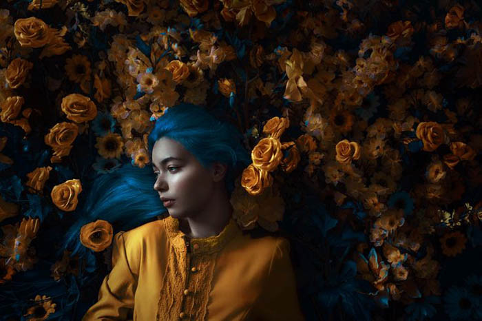 Adi Dekel portrait of a young woman with blue hair dressed in a gold shirt and surrounded by gold roses