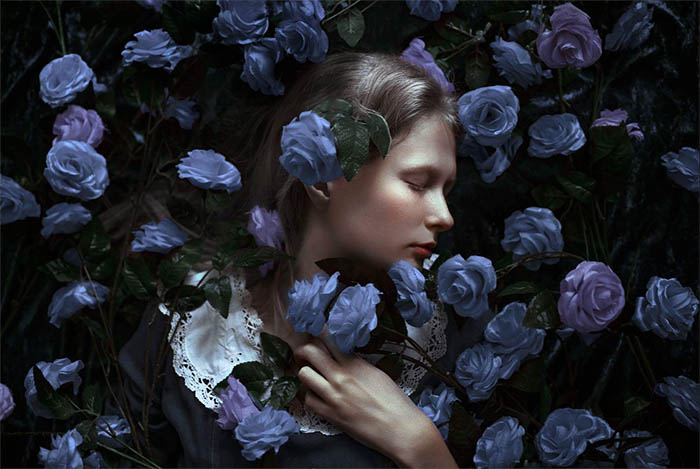 Adi Dekel fine art portrait of a young woman surrounded by blue flowers