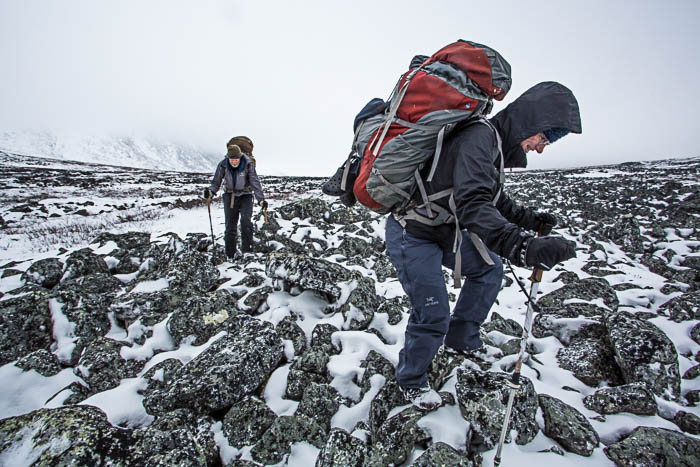 Photo of two people wearing backpacks hiking in snow covered mountains