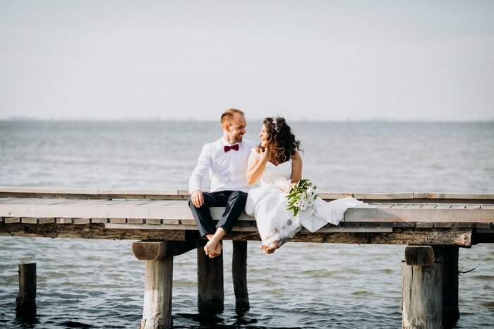 Bride and Groom posing on a jetty