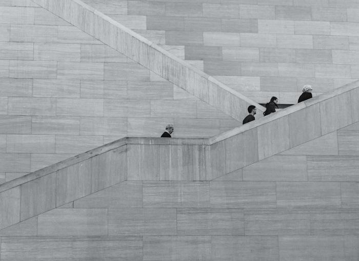 Foto em escala de cinza de pessoas subindo escadas de pedra