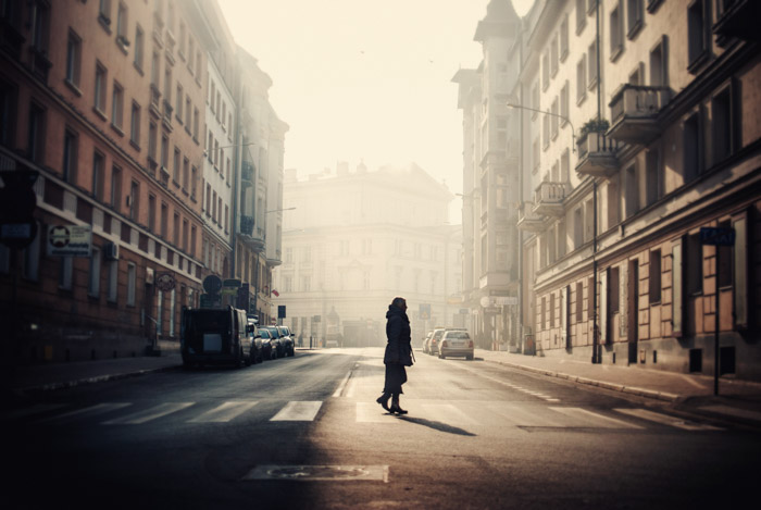 Foto escura de uma mulher atravessando a rua