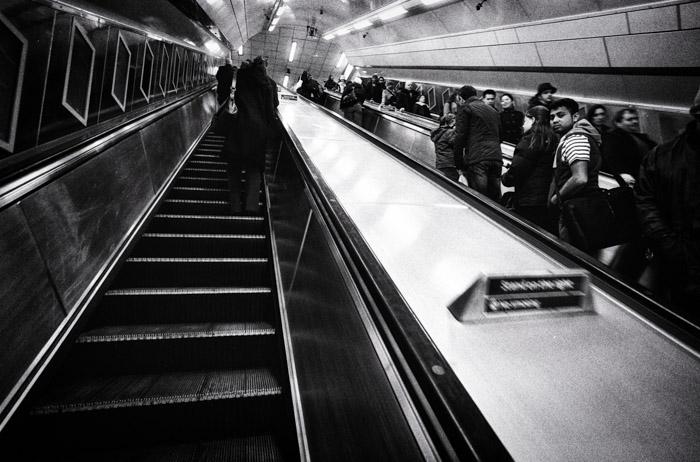 Imagem em preto e branco de pessoas no elevador de uma estação de metrô