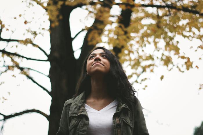 Composição de baixo ângulo de uma mulher na frente de árvores