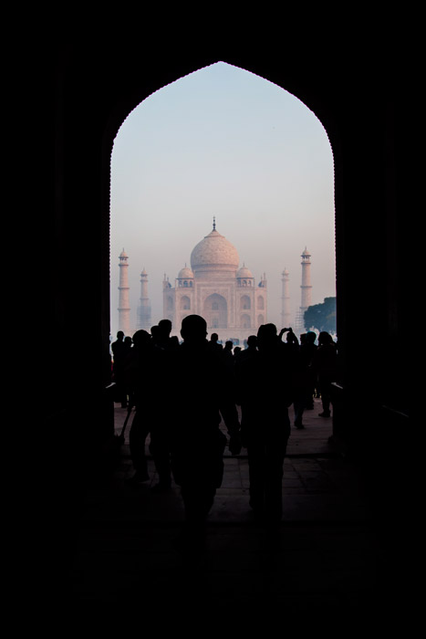 A crowd walking towards the Taj mahal framed by an archway